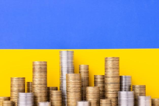 ウクライナの旗の前に金と銀のお金のスタック