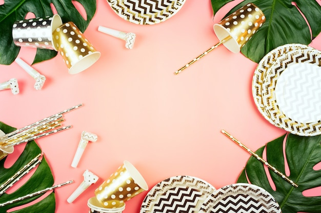 黄金と銀の紙コップ、皿とストロー、角とモンステラの葉がテーブルに。ピンクの背景。パーティーのコンセプトです。
