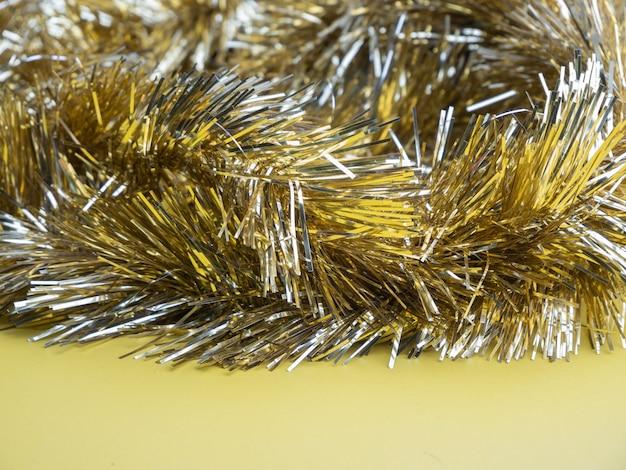 Золотая и серебряная мишура, рождественский орнамент на желтом