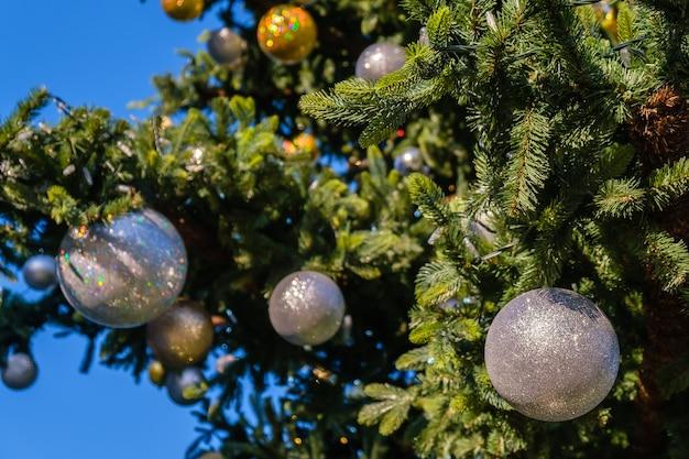 屋外のクリスマスツリーに金と白の新年の装飾と花輪