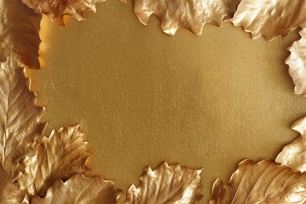 Golden autumn background. metallic oak leaves frame a shiny surface.