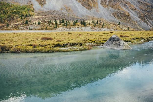 森の丘の中腹を望むマウンテンクリークの大きな石と黄金の秋の風景。秋のターコイズブルーの澄んだ水の流れの美しい大きな岩。透明な水の中の緑の波紋砂底。