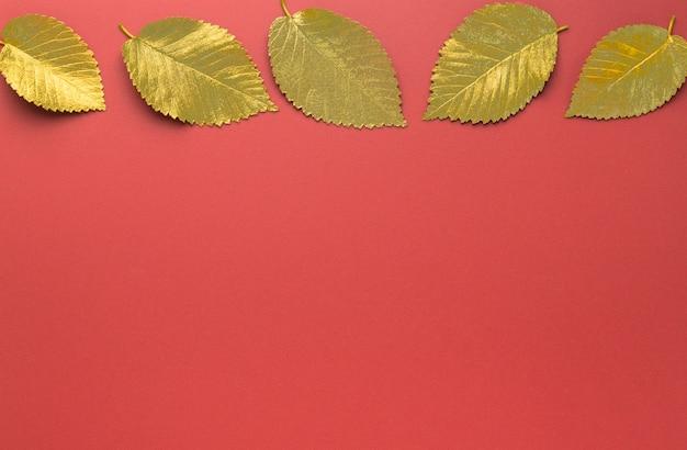 Золотые осенние листья в горизонтальной рамке на красном фоне осенняя концепция вид сверху осенних листьев ...