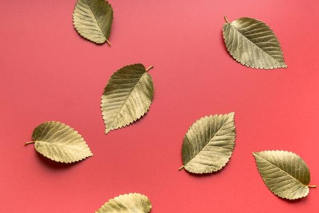 Золотые осенние листья на красном фоне осенняя концепция вид сверху осенних листьев в золотой краске