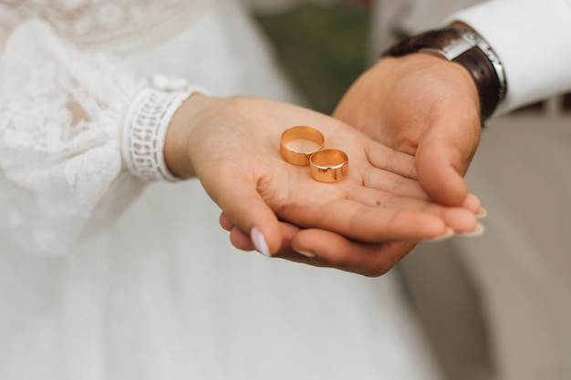 Golden bands in the hands of groom and bride