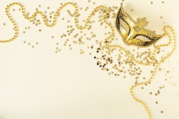 Золотые бусы и карнавальная маска с золотыми звездами конфетти на бежевом фоне шампанского. плоская планировка. скопируйте пространство.