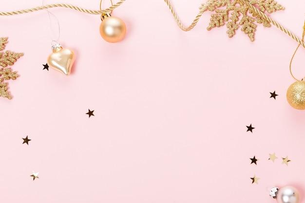 Золотые красивые сверкающие рождественские декоративные игрушки на пастельно-розовом фоне.