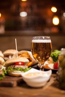 나무 테이블에 맛있는 햄버거 옆에 황금 맥주. 감자 튀김. 그린 샐러드. 감자 튀김. 마늘 소스.