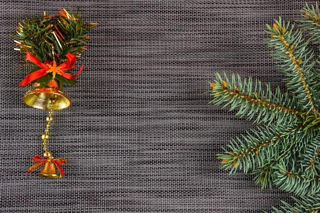 구리 공간이 있는 회색 새해 배경에 있는 크리스마스 트리의 가지인 골든 벨. 크리스마스 장식.