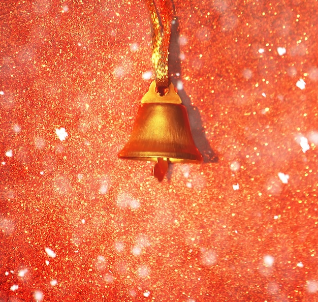 Golden bell on glitter decorative background with snow effect.