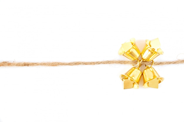 Golden bells on a brown rope with a white background, it is designed decoration for christmas