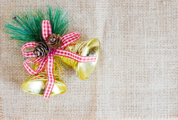Golden bells christmas with red ribbon and pines on the sack