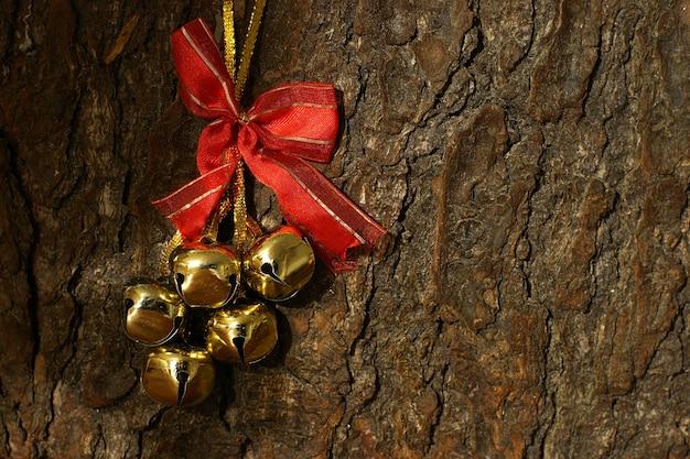木の樹皮にある金色の鐘。上部に赤いリボンがあり、テキストを配置します。