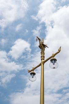 Golden bird sculpture on the top of eletrical lamp.