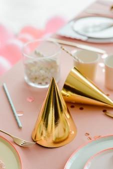 ピンクのパーティーテーブルの上の黄金の誕生日キャップ