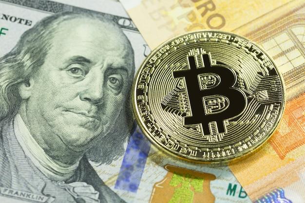Golden bitcoin on 100 dollar and euro bills