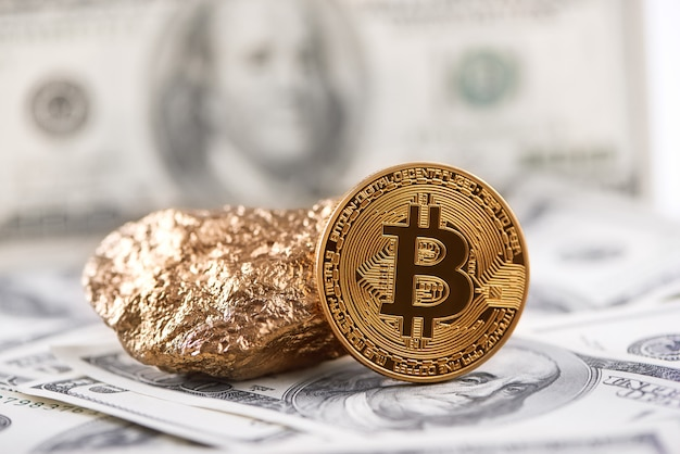 Golden bitcoin as main world cryptocurrency and gold lump presented on dollar banknote background.