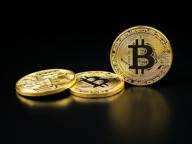 Golden bitcoin on black .