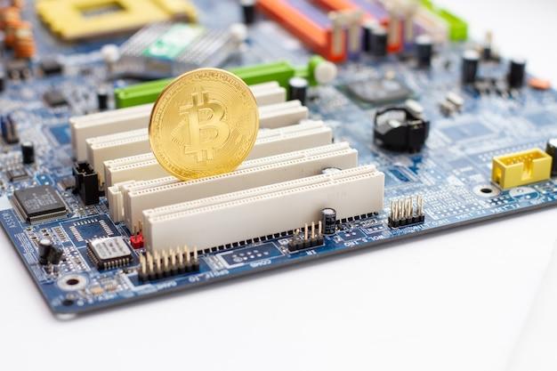 Golden bitcoin on the circuit main computer board.