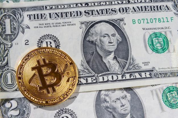 Золотая монета биткойн и банкноты двух американских долларов