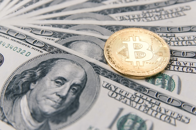 Golden bitcoin coin on banknotes of one hundred us dollar. cryptocurrency business concept. exchange bitcoin cash for a dollar. virtual money investment.