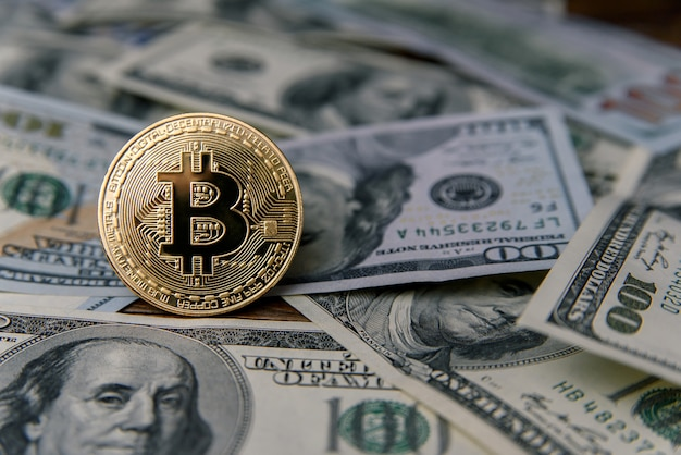 Golden bitcoin coin on banknotes of one hundred us dollar. virtual money investment. cryptocurrency business concept. exchange bitcoin cash for a dollar.