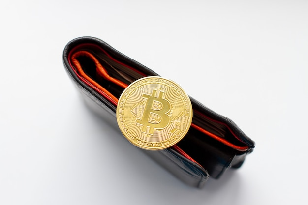 Golden bitcoin coin on black leather wallet.