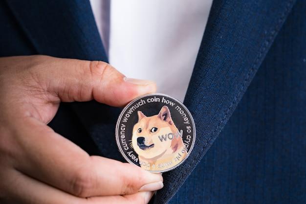금색 비트코인 코인 dogecoin doge 그룹은 파란색 양복을 입은 사업가의 손에 cryptocurrency가 포함되어 있습니다. 파일링하고 넣어 나에게. 닫기 및 매크로 사진 개념입니다.