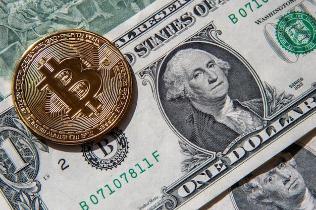 Золотая монета биткойн сверху банкноты одного и двух американских долларов