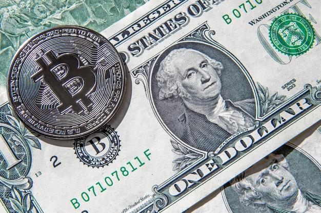 Золотая монета биткойн сверху банкноты одного и двух американских долларов Premium Фотографии