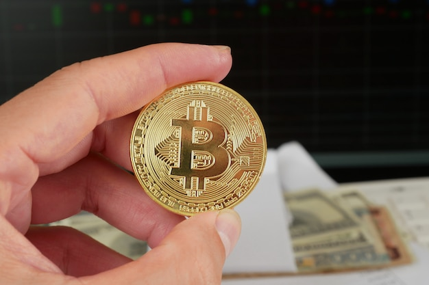 Golden bitcoin coin in hand holding with multiple banknotes and graphs