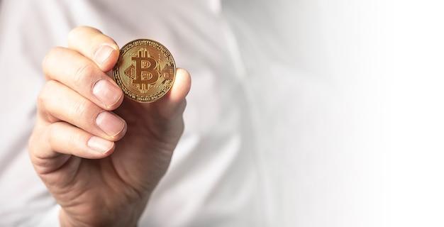 男性の手の黄金のビットコインコインがクローズアップ。コピースペース付きのバナー。
