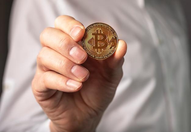 男性の手の黄金のビットコインコインがクローズアップ。