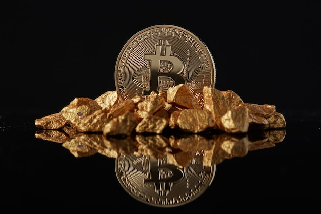Golden bitcoin coin and mound of gold with reflection. concept of financing bitcoin cryptocurrency in noble metal
