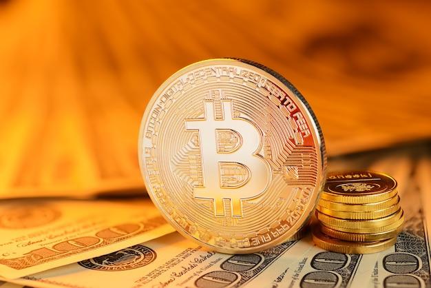 Золотая монета биткойн на купюрах в разных валютах