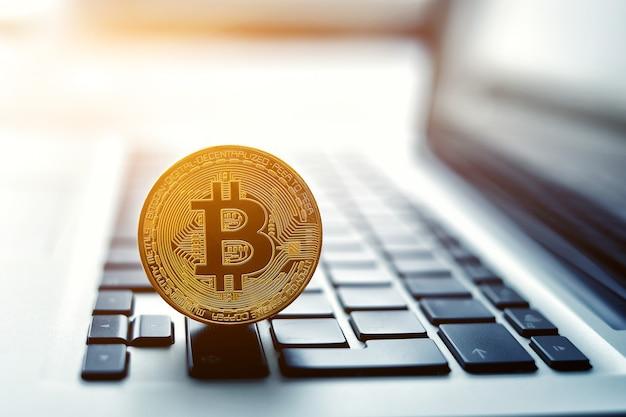ノートパソコンのキーボードのゴールデンビットコインコイン。取引の概念