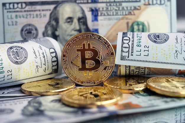 Золотая монета биткойн на долларах сша крупным планом