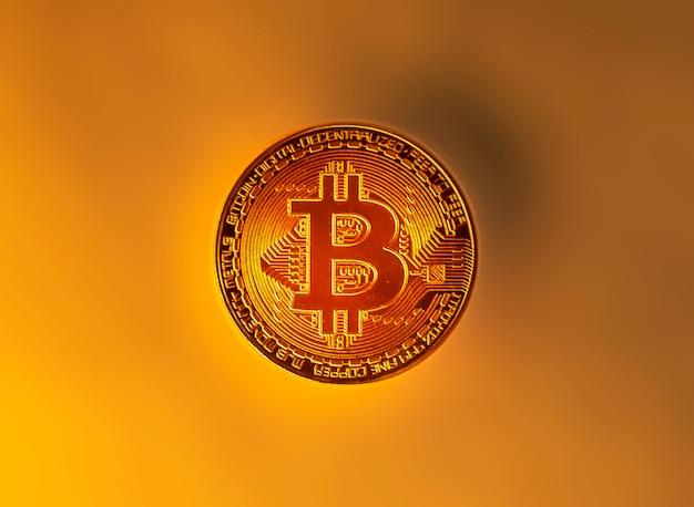 노란색 단색 배경에 황금 bitcoin 동전입니다.