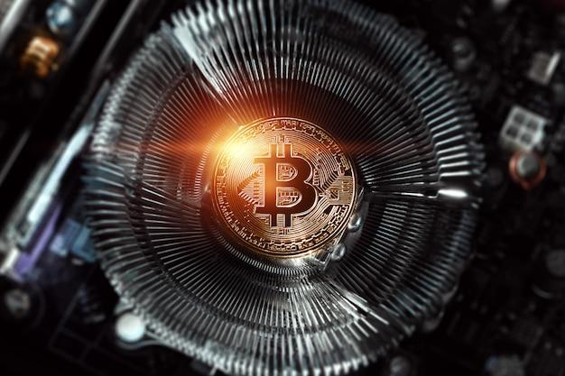 Golden bitcoin on the computer board