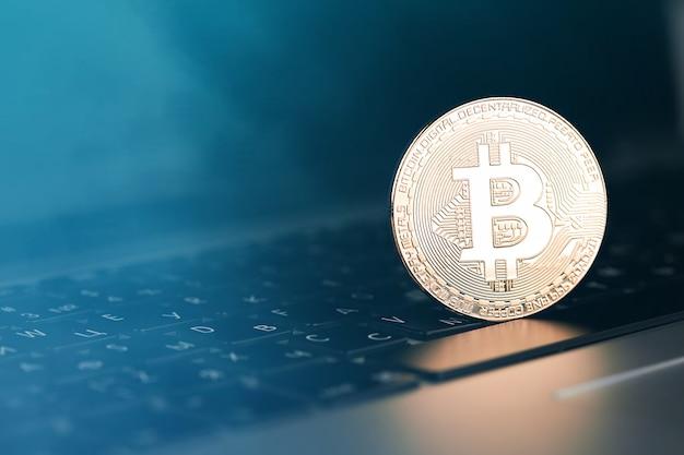 Golden bitcoin on computer keyboard, closeup. bitcoins and virtual money