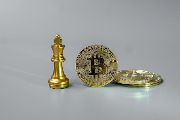 ゴールデンビットコイン暗号通貨コインスタックとチェスキングピース。