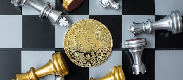 Golden bitcoin cryptocurrency coin stack and chess piece on chessboard.