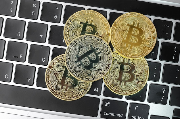 Golden bitcoin cryptocurrency coin stack on laptop keyboard.