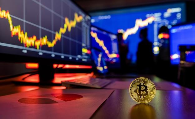 Золотой токен криптовалюты bitcoin на столе перед отчетом о росте торговли диаграммой графика финансового анализа на экране компьютера и ноутбука во время встречи брокера в тени размытым фоном.