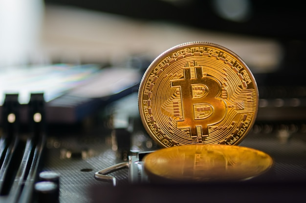 Golden bitcoin on electronic board