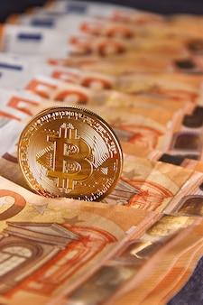 Golden bitcoin on fifty euro banknotes background. bitcoin crypto currency, blockchain technology, digital money, mining concept, bitcoin on 50 euro bill.