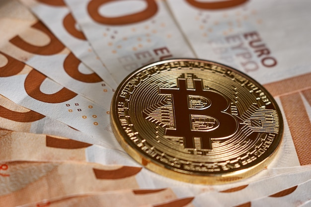 Golden bitcoin on fifty euro banknotes background. bitcoin crypto currency, blockchain technology, digital money