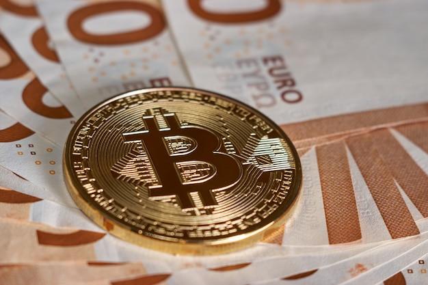 Golden bitcoin on fifty euro banknotes