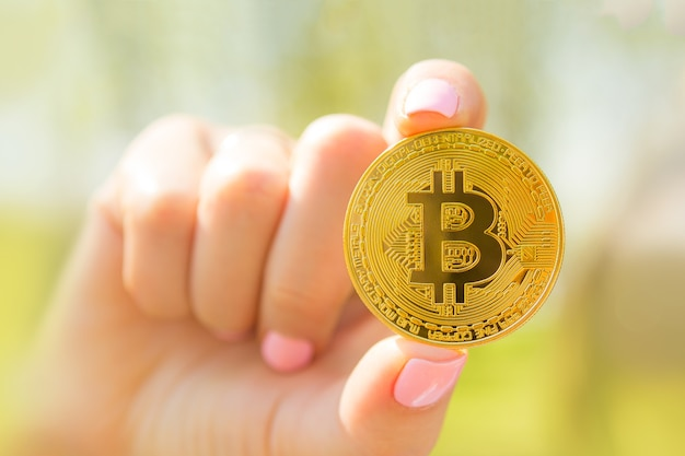 Golden bitcoin in girls hand with pink nails outside