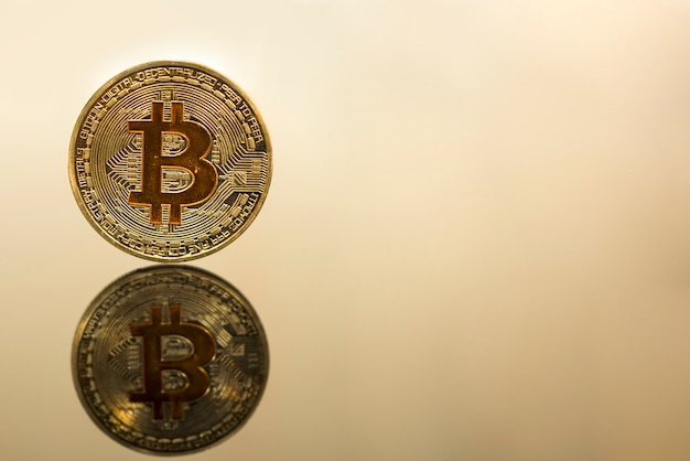 Golden bitcoin on glass table. abstract photo of virtual cryptocurrency.